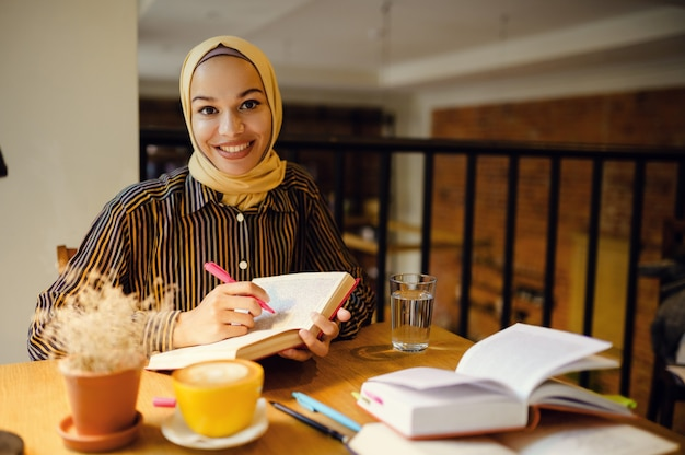 Smiling arab girl in hijab holds notebook, university cafe interior on background. muslim woman with books sitting in library.