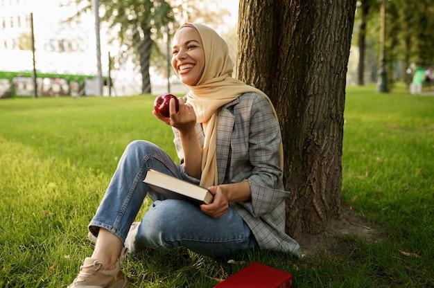 히잡에 웃는 아랍 소녀는 여름 공원에서 사과와 교과서를 보유하고 있습니다. 잔디밭에 쉬고 책과 무슬림 여성입니다.