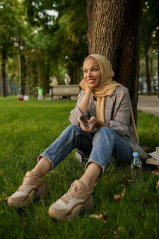 여름 공원에서 hijab에 웃는 아랍 소녀. 잔디밭에 쉬고 이슬람 여성입니다.