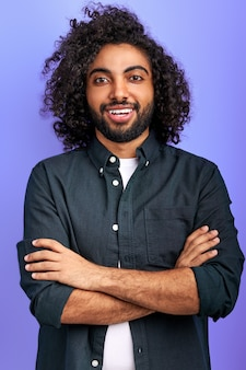 Smiling arab male posing at camera with crossed arms, young handsome guy smiles, shine with happiness isolated over purple space