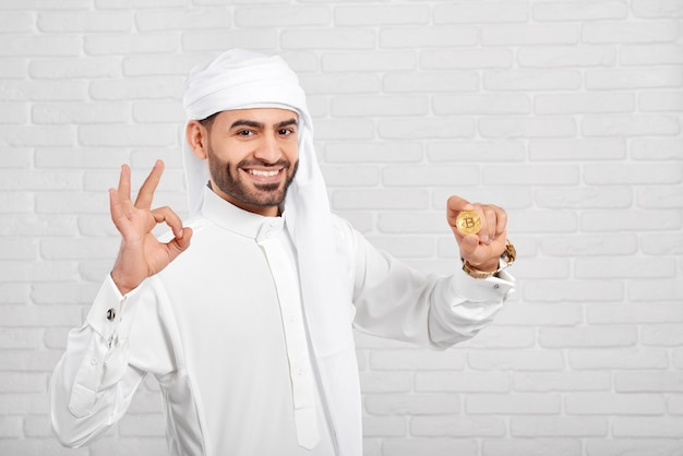 Smiling arabian man keeps bitcoin and looks very happy, standing on white background.