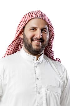 흰색 스튜디오 배경에 격리된 웃고 있는 아라비아 남자의 초상화. 국적, 문화, 포용, 다양성. 머리 스카프와 전통적인 중동 옷에 자신감이 사업가. 사업.