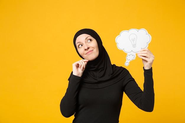 Улыбающаяся арабская мусульманка в черной одежде хиджаба держит в руках, говорит облако с лампочкой, изолированной на портрете на желтой стене. концепция религиозного образа жизни людей. .