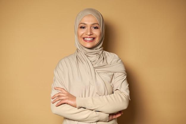 コピースペースとベージュの表面に腕を組んでポーズをとるアラビアのイスラム教徒の女性の笑顔