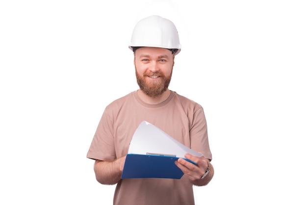 Улыбающийся архитектор, глядя на эскизы на белом