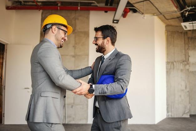 건설 과정에서 건물에 서있는 동안 사업가와 악수하는 건축가 웃 고.