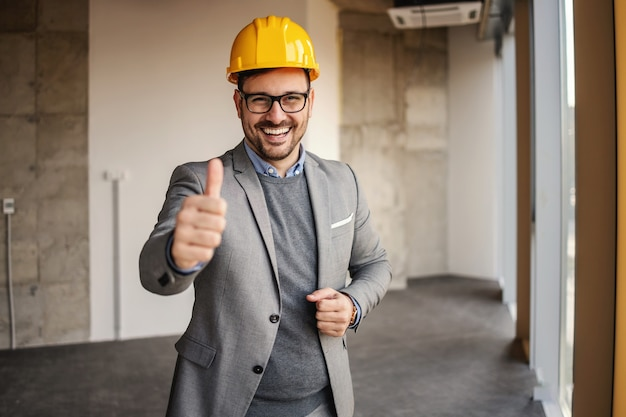 Smiling architect standing in building in construction process and showing thumbs up.