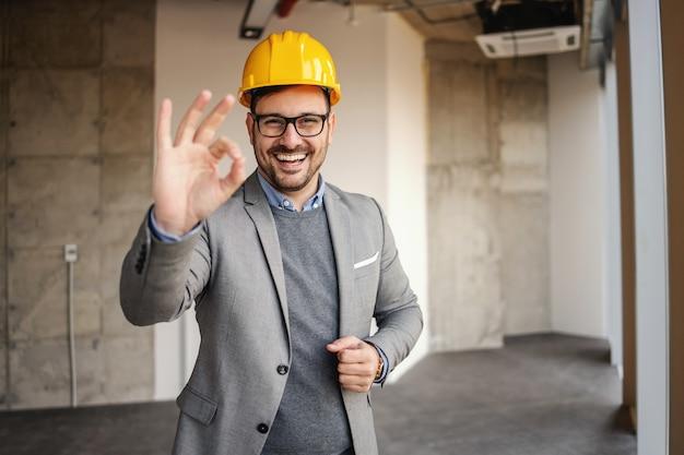 건설 과정에서 건물에 서서 괜찮아 제스처를 보여주는 웃는 건축가.