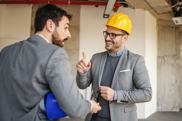 Smiling architect talking to investor while standing in building in construction process.