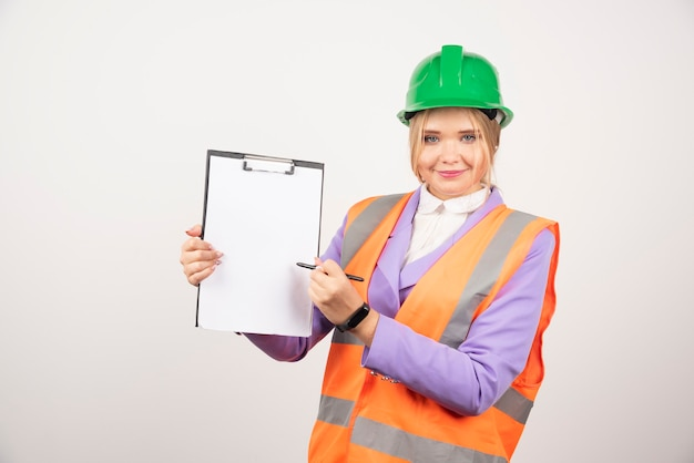 Donna sorridente dell'architetto in elmetto protettivo con la compressa su bianco.