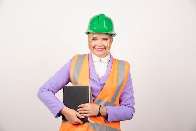 Donna sorridente dell'architetto in compressa della tenuta del casco su bianco.