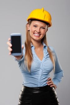 Smiling architect woman showing screen of smart phone