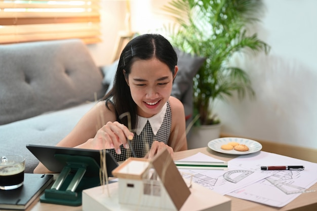 コンピューターのタブレットと青写真で自宅で働く笑顔の建築家の女性。