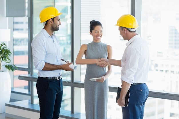 Smiling architects shaking hands with each other
