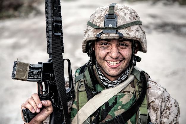 웃는 군대 군인, 위장 전투 유니폼을 입은 미국 해병대 보병 사수, 방탄복과 헬멧으로 보호, 시골 길 근처에 서있는 동안 손에 돌격 소총을 들고 포즈
