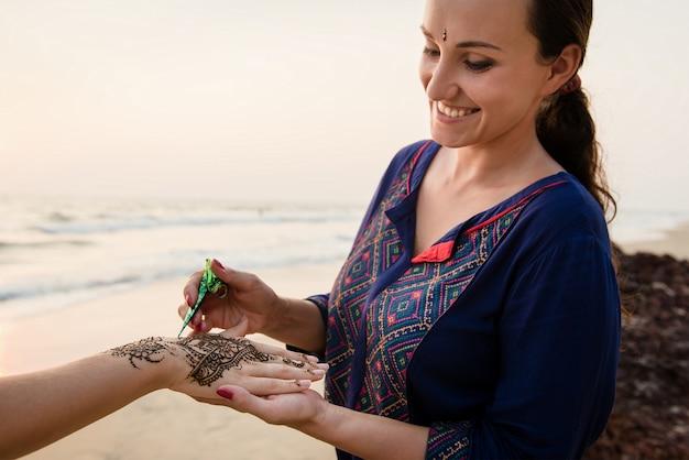 Улыбающийся художник, применяющий татуировку хной на руках женщин на открытом воздухе. менди - традиционное индийское декоративное искусство.