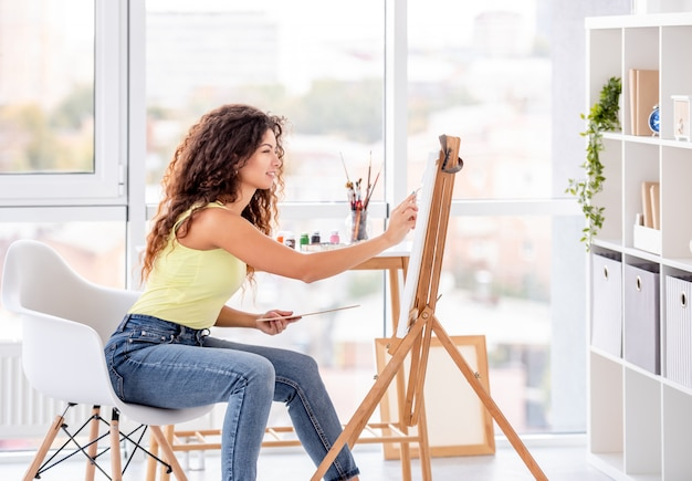 Smiling artist painting on easel