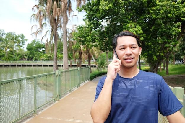 公園でスマートフォンと話している笑顔のアサイン男。テクノロジーとライフスタイルのコンセプト