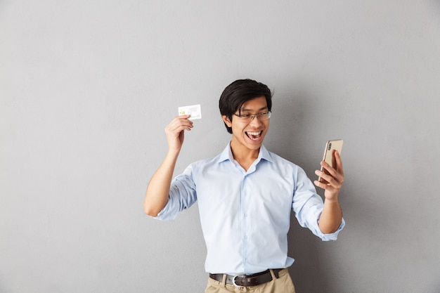 Smiling asian business man standing isolated, holding mobile phone, showing plastic credit card