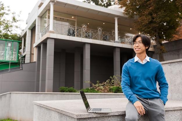 屋外でラップトップコンピューターを使用して笑顔のアジアのビジネスマン