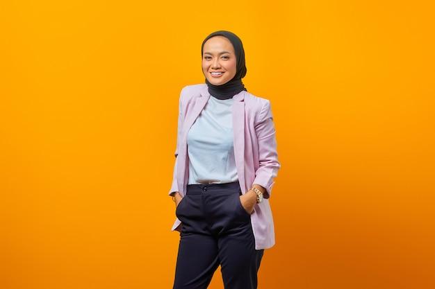 노란색 배경 위에 카메라를 보고 웃는 아시아 비즈니스 여성