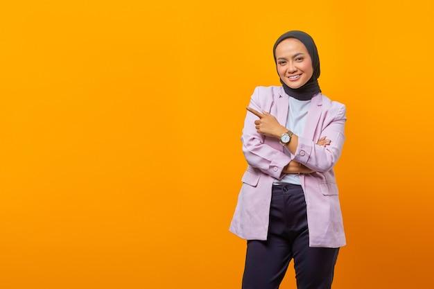노란색 배경 위에 카메라를 쳐다보며 웃고 있는 아시아 비즈니스 여성