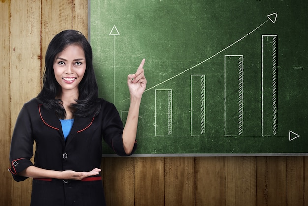 Smiling asian business woman showing a incrasing graph