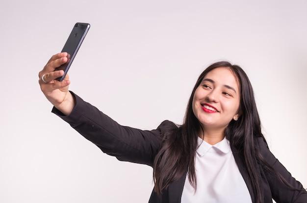 Улыбающаяся азиатская бизнес-леди, делающая селфи со смартфоном на белом.