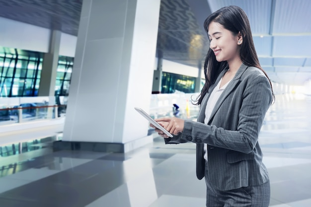 Smiling asian business woman using digital tablet