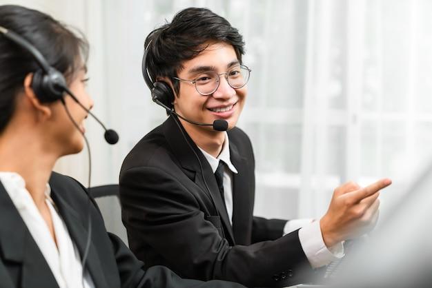 직장에서 고객 지원 전화 교환원의 마이크 헤드셋을 착용한 웃고 있는 아시아 사업가 컨설턴트.