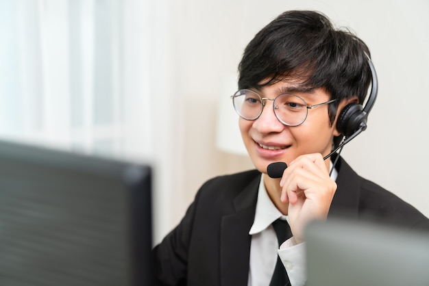 Smiling asian businessman consultant wearing a microphone headset of customer support phone operator