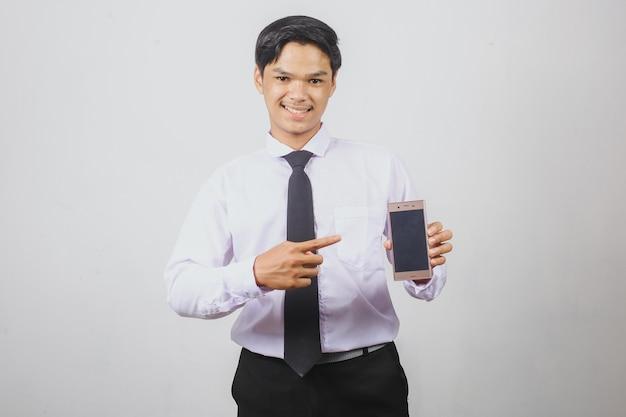 스마트 폰의 빈 화면을 가리키는 흰색 셔츠와 검은 넥타이에 웃는 아시아 사업가