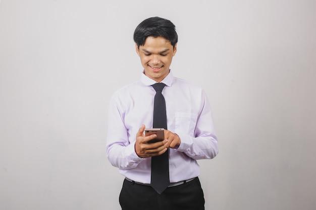 흰 셔츠와 검은 넥타이를 입고 서서 스마트 폰을 사용하는 웃고 있는 아시아 사업가