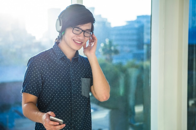 Smiling asian businessman listening to music in office