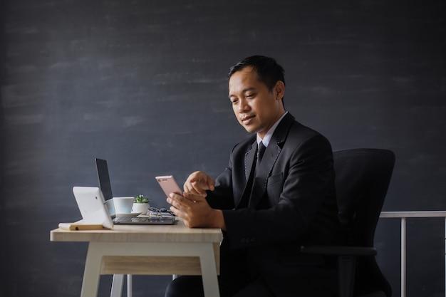 笑顔のアジアのビジネスマンがオフィスの机の上のスマートフォンを探して指さします。