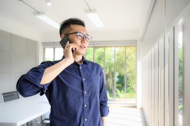 窓際に立って彼の電話で話している笑顔のアジア人ビジネスマン