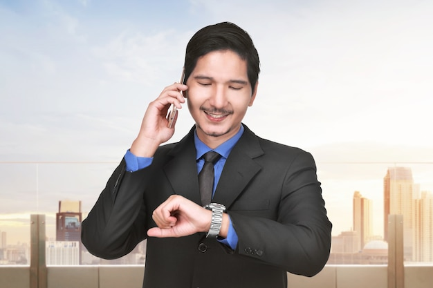 Smiling asian businessman talking on the mobile phone while checking time