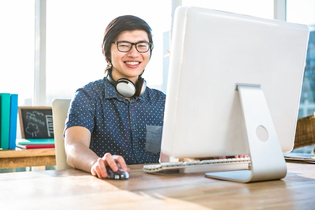 Smiling asian businessman using computer in office
