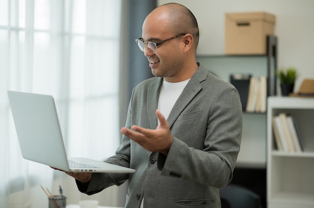 笑顔のアジア人ビジネスマンが在宅勤務のビデオ会議から仕事をしています。