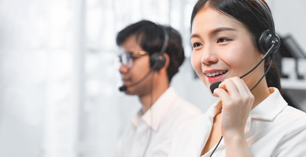 Smiling asian businesswoman consultant wearing microphone headset of customer support phone operator at workplace.