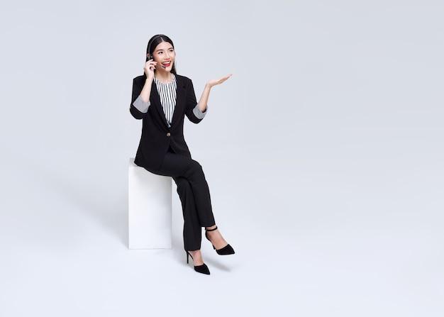 灰色の背景に分離された笑顔のアジアの実業家カスタマーサポート電話オペレーター。コールセンターとカスタマーサービスのコンセプト。