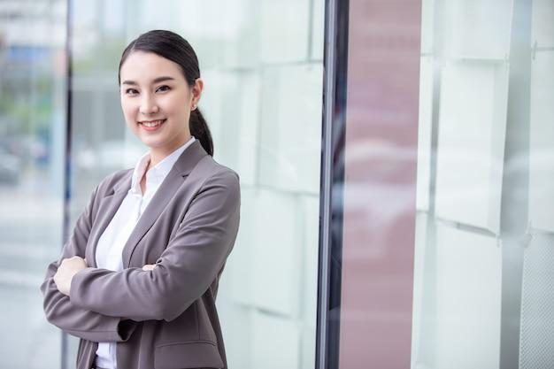 흐림 사무실 건물에 웃는 아시아 사업가