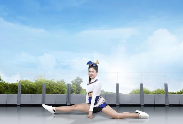 Smiling asian cheerleader doing splits