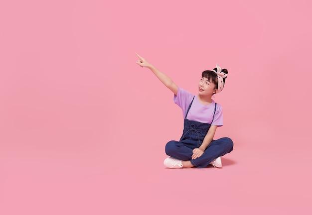 Улыбающаяся азиатская девочка ребенка указывая пальцем на пустое пространство рядом с розовой изолированной стеной.