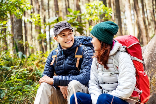 Smiling asian couple hikers with backpack looking at each other