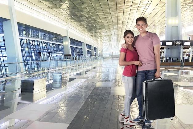 旅行に荷物の袋を持って笑顔のアジアカップル