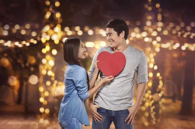 Smiling asian couple holding red heart shape