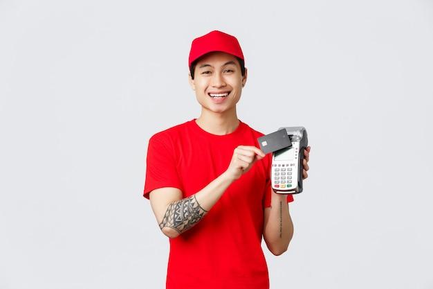 Улыбающийся азиатский курьер в красной кепке и форме футболки прижимает кредитную карту к платежному терминалу для бесконтактной оплаты заказов клиентов. доставщик объясняет способ оплаты, стоя на сером фоне