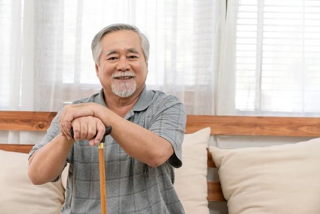 웃고 있는 아시아 노인은 지팡이를 들고 건강하게 은퇴하고 집 거실에 있는 소파에 앉아 휴식을 취합니다