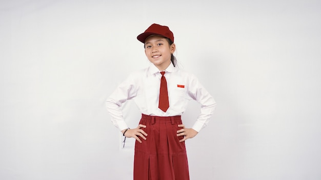Smiling asian elementary school girl hands on waist isolated on white background